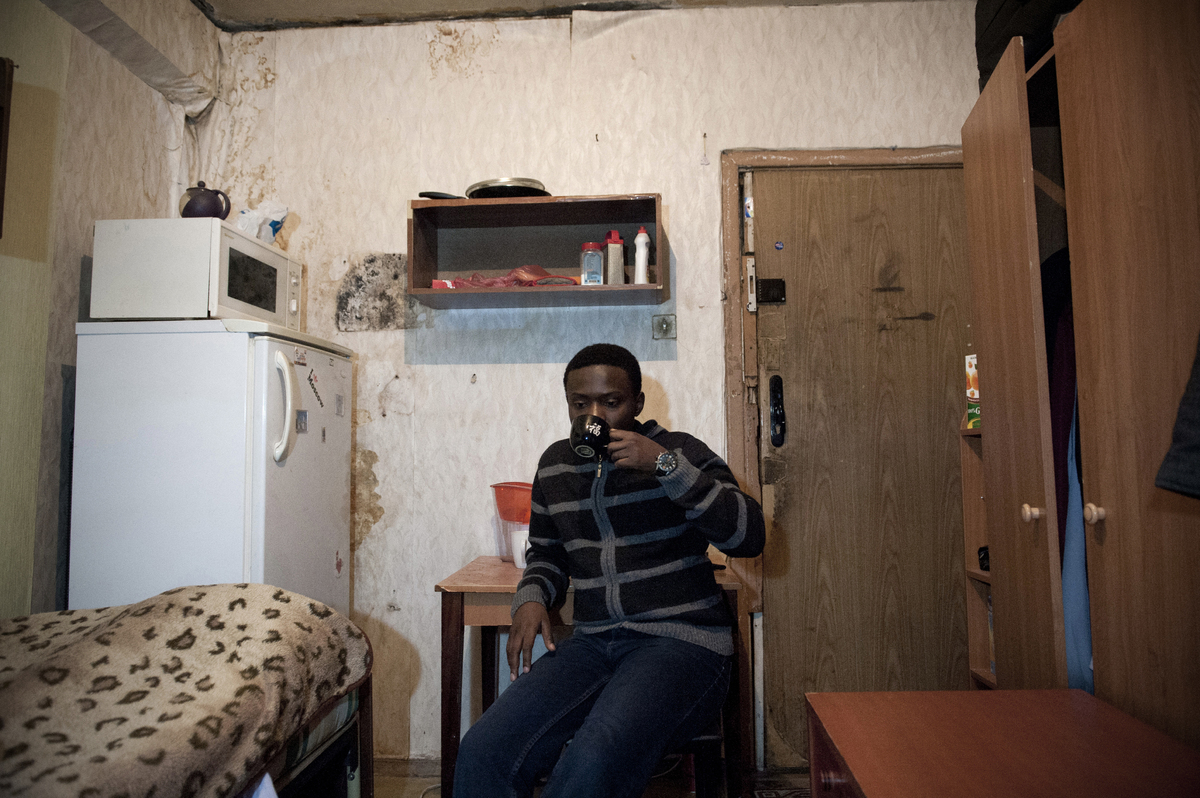 Kudakwashe Ndlova, a 25-year-old student from Zimbabwe, drinking tea in a room he shares with a Russian  student.