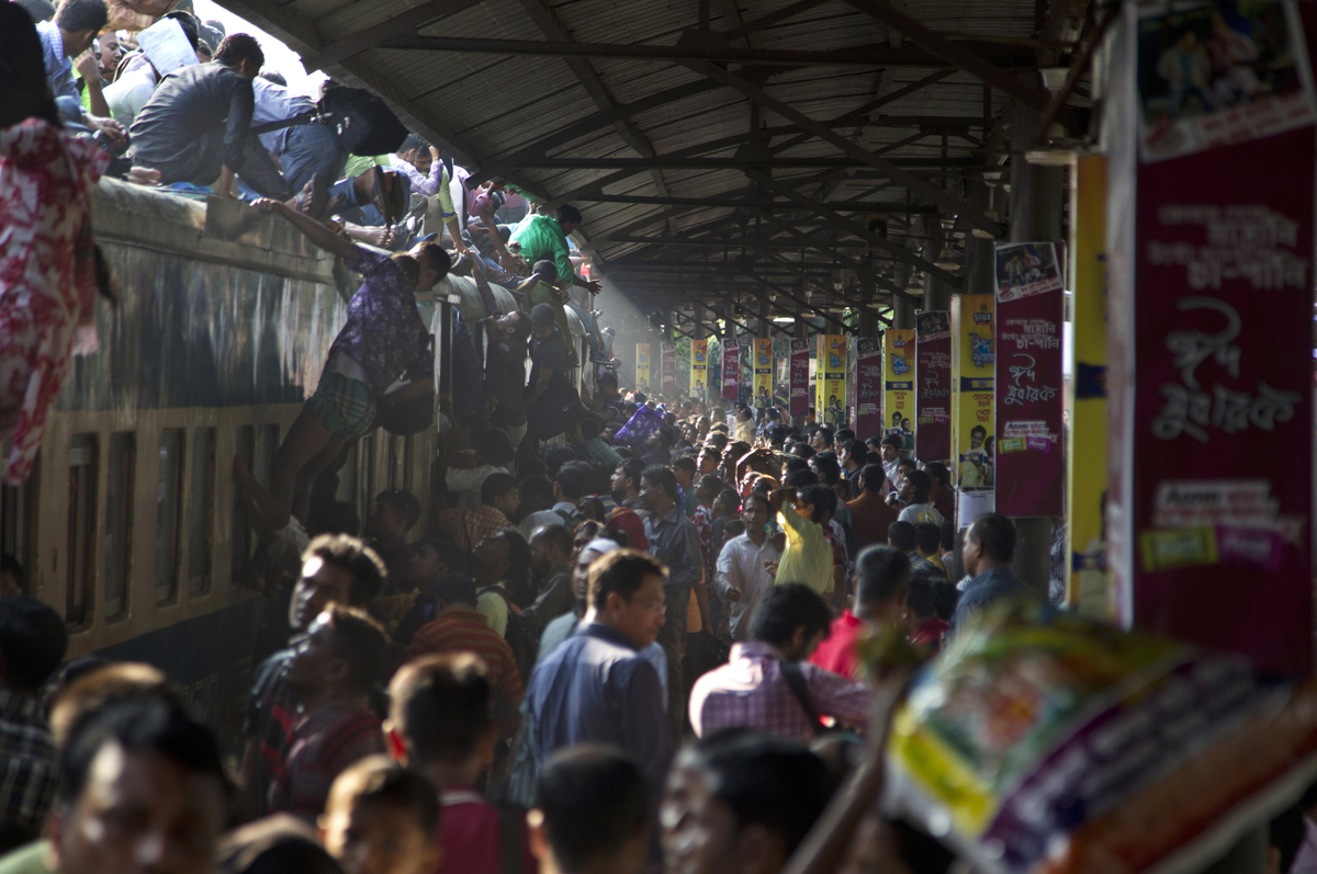 Bangladeshi Muslims try to climb on to the roof of an overcrowded train as they head to their homes ahead of Eid al-Adha in D