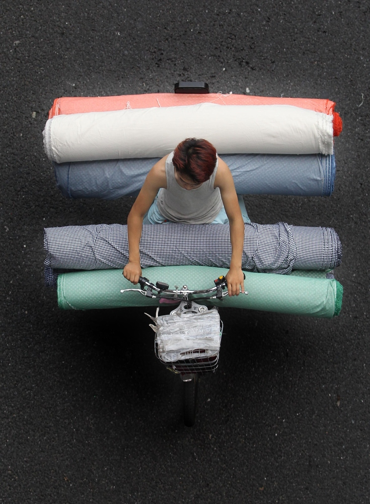 A porter rides a tricycle carrying clothes and people at Guangzhou International Textile City on May 27, 2014 in Guangzhou, C