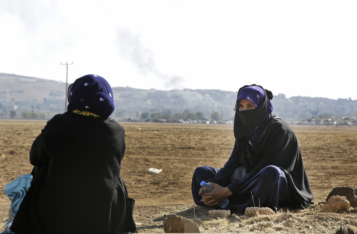 Turkish Kurds pictured on the outskirts of Suruc, on the Turkey-Syria border, as smoke rises  in the background from a strike
