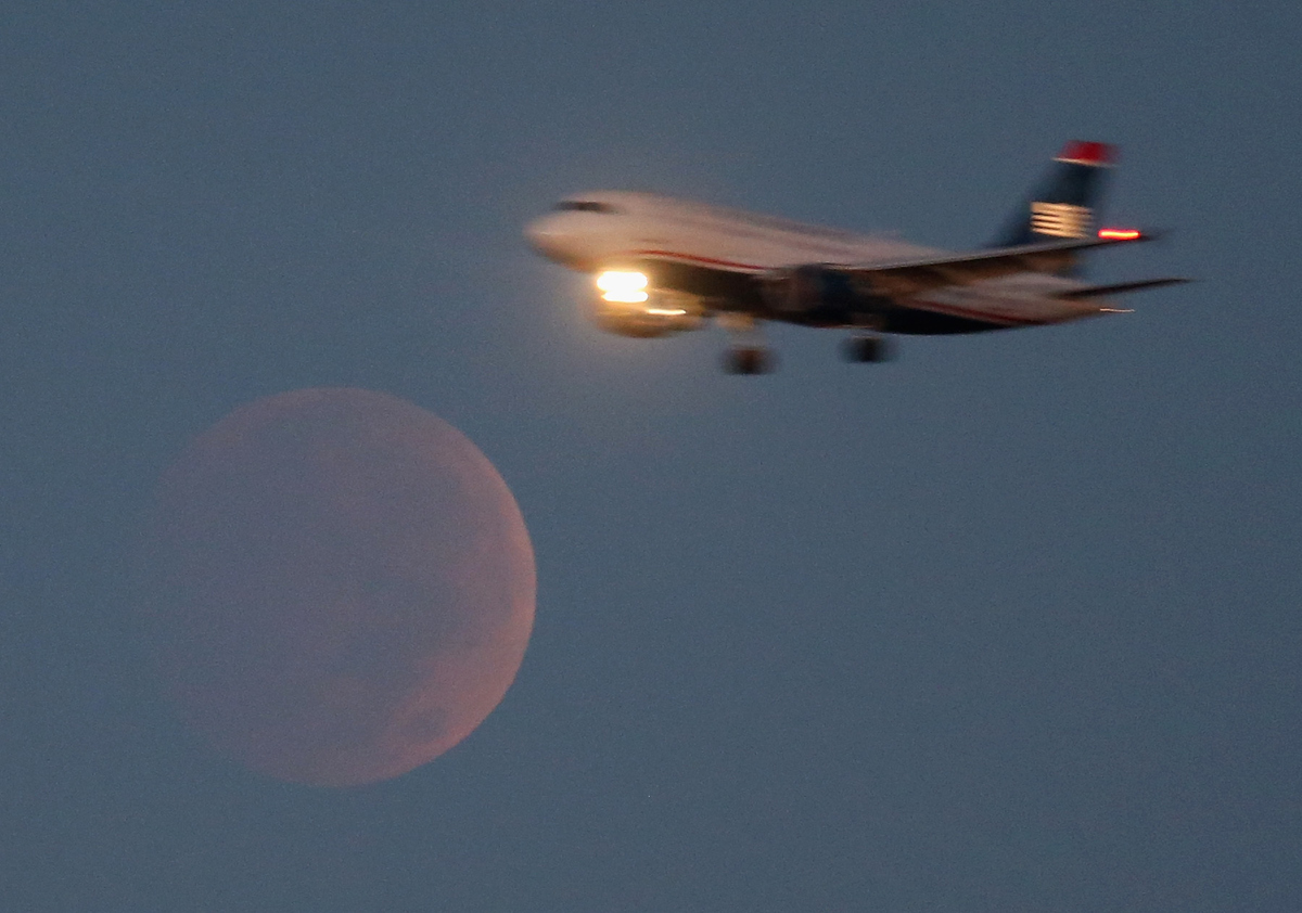 A commercial airliner on approach to Reagan National Airport flies past the full moon during the eclipse.