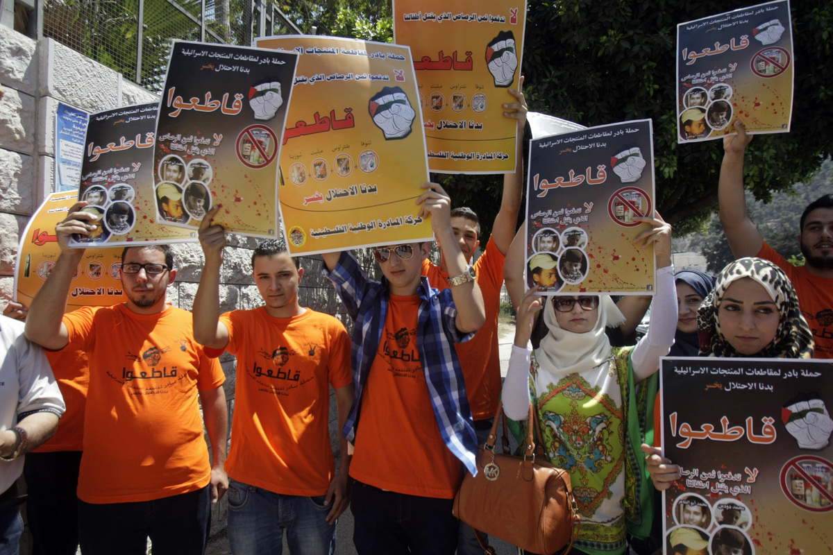 Palestinian activists hold posters during a demonstration calling for a boycott of Israeli products to protest Israel's milit