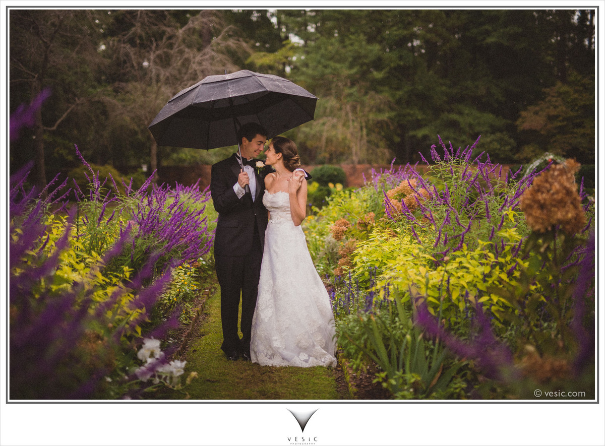 """""""Robert and Sarah try and evade the rain during their outdoor ceremony at Weymouth Center in Southern Pines, North Carolina."""""""