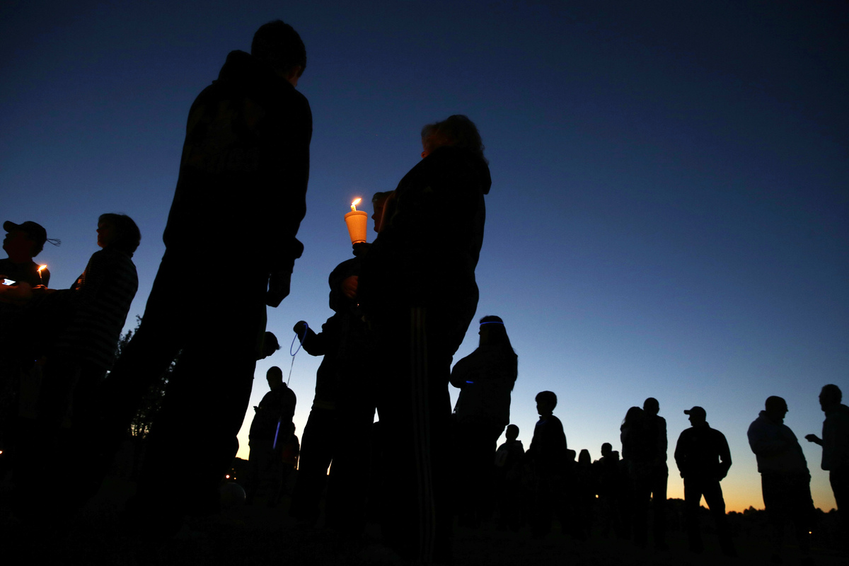 People hold candles as they gather for an anti-bullying rally Sunday, Oct. 12, 2014, in Sayreville, N.J. The central New Jers