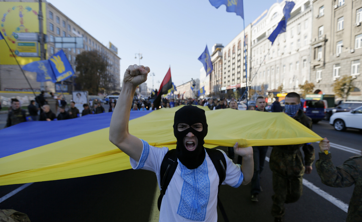 Demonstrators shout slogans during a Svoboda party rally in Kiev, Ukraine, Tuesday, Oct. 14, 2014. (AP Photo/Sergei Chuzavkov