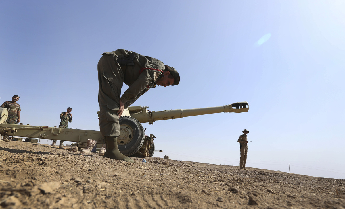 FILE - In this Oct. 1, 2014, file photo, a Kurdish peshmerga soldier prays at a battle field in Mahmoudiyah, Iraq, after Kurd