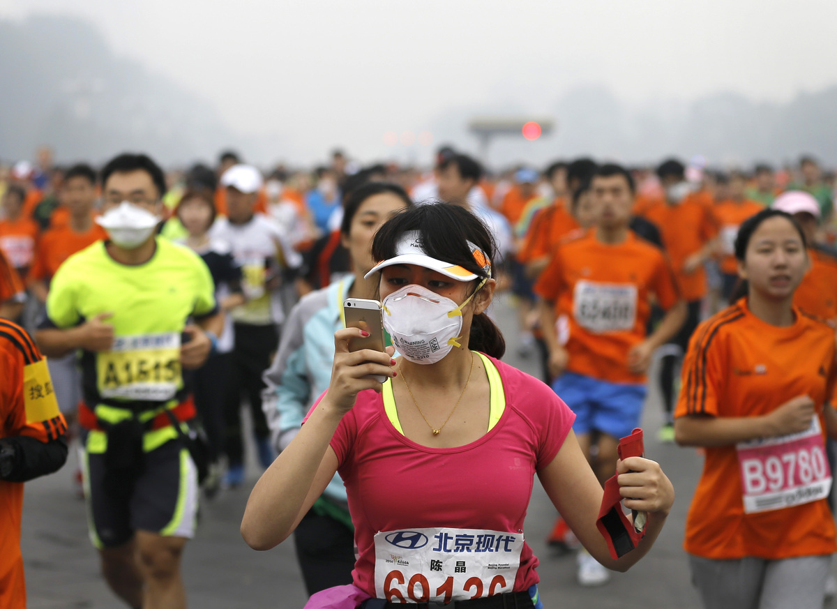In this Sunday, Oct. 19, 2014 photo, a runner, wearing a mask to protect herself from pollutants, looks at her smartphone as