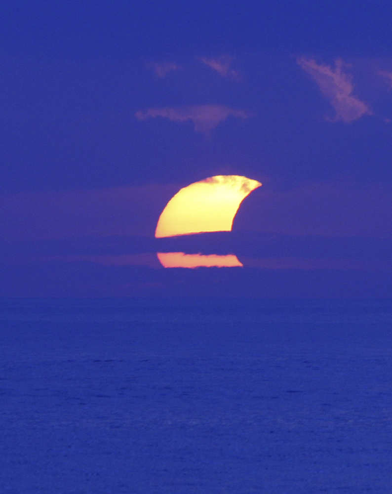 A partial solar eclipse is seen through cloud at Sanur beach, Bali, Indonesia, Friday, May 10, 2013.