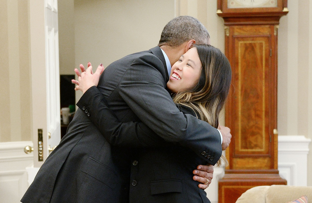 President Barack Obama gives a hug to Dallas nurse Nina Pham in the Oval Office of the White House on October 24, 2014 in Was