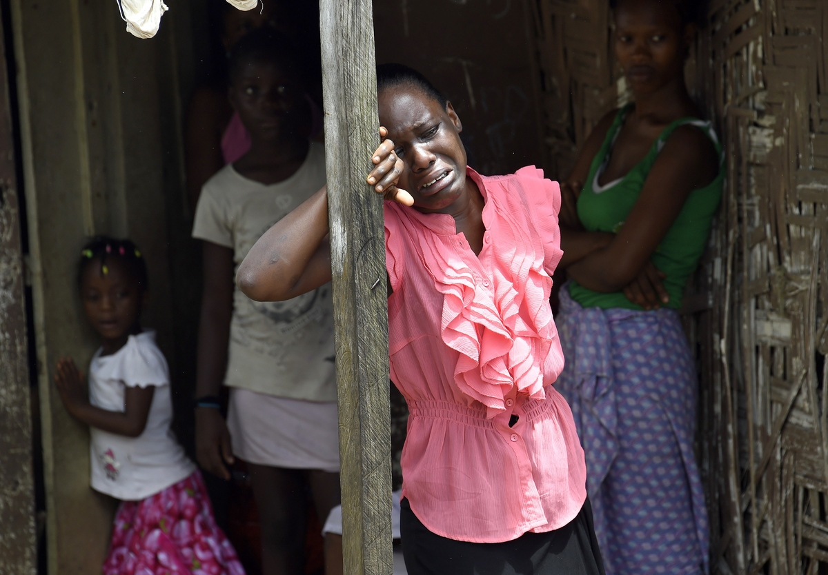 A woman reacts after a relative is suspected of dying from the Ebola virus, in the Liberian capital Monrovia