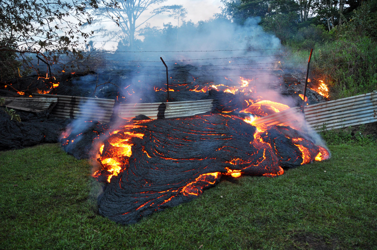 This Tuesday, Oct. 28, 2014 photo provided by the U.S. Geological Survey shows lava that has pushed through a fence marking a