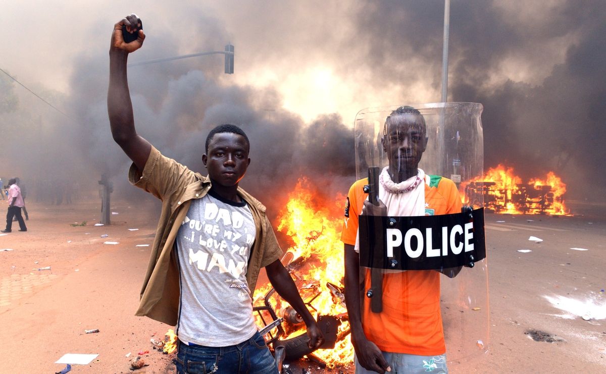 Protesters pose with a police shield outside the parliament in Ouagadougou as cars and documents burn outside Oct. 30, 2014.