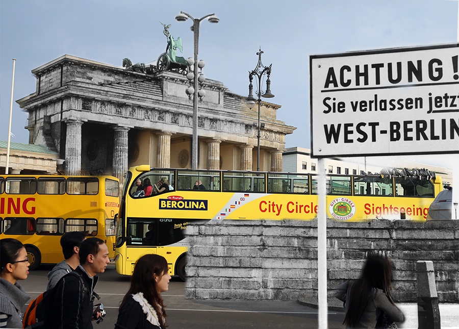 Tourists and tourist buses pass by the Brandenburg Gate on April 3, 2014 in Berlin, Germany. In black and white a sign reads: