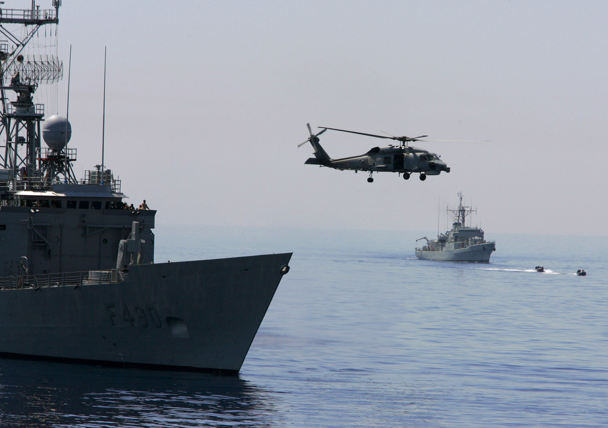 A Turkish Navy Blackhawk helicopter takes off from the Turkish frigate Gaziantep, left, as French Navy destroyer Piquet, righ