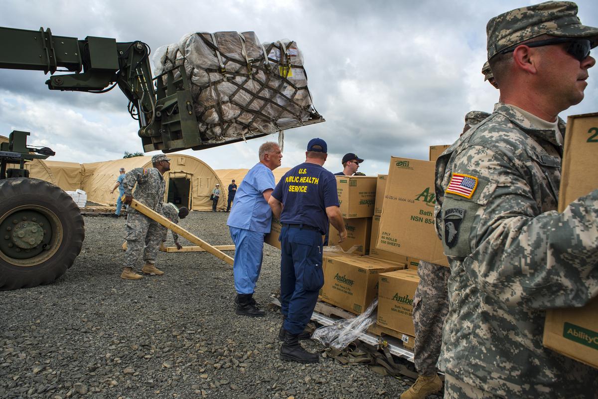 MONROVIA, LIBERIA-NOVEMBER 4:   U.S. military and the U.S. Public Health Service (USPHS) staff unload cargo at the Monrovia M