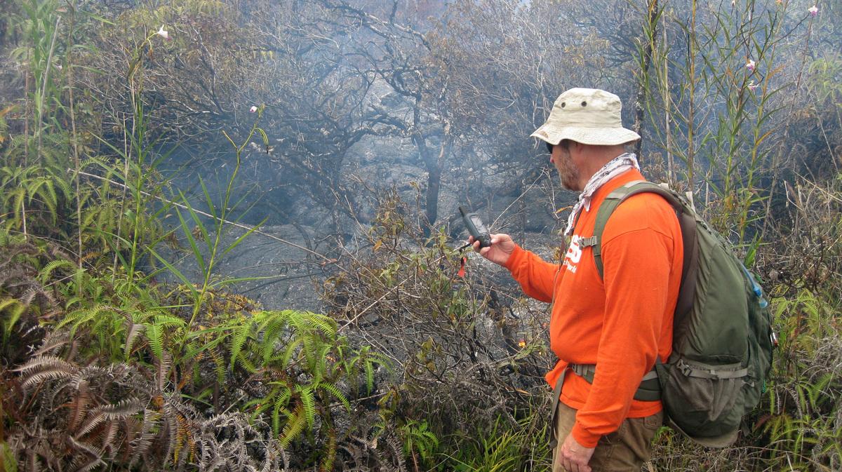 A geologist taking a GPS waypoint of the leading edge of the lava flow near the town of Pahoa on the Big Island of Hawaii. Th