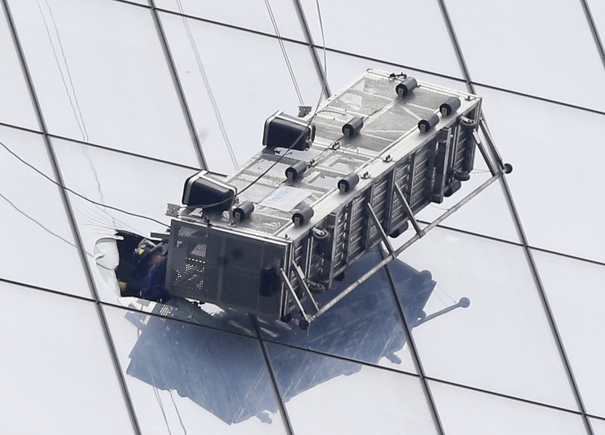 A firefighter reaches through a cut-out window into a dangling work basket to rescue two workers from outside the 104-story 1
