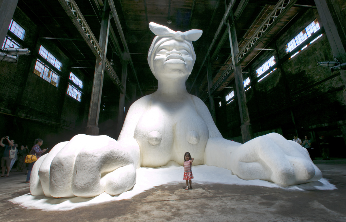 "A young girl stands in front of ""A Subtlety or the Marvelous Sugar Baby,"" by artist Kara Walker, on display inside the fo"