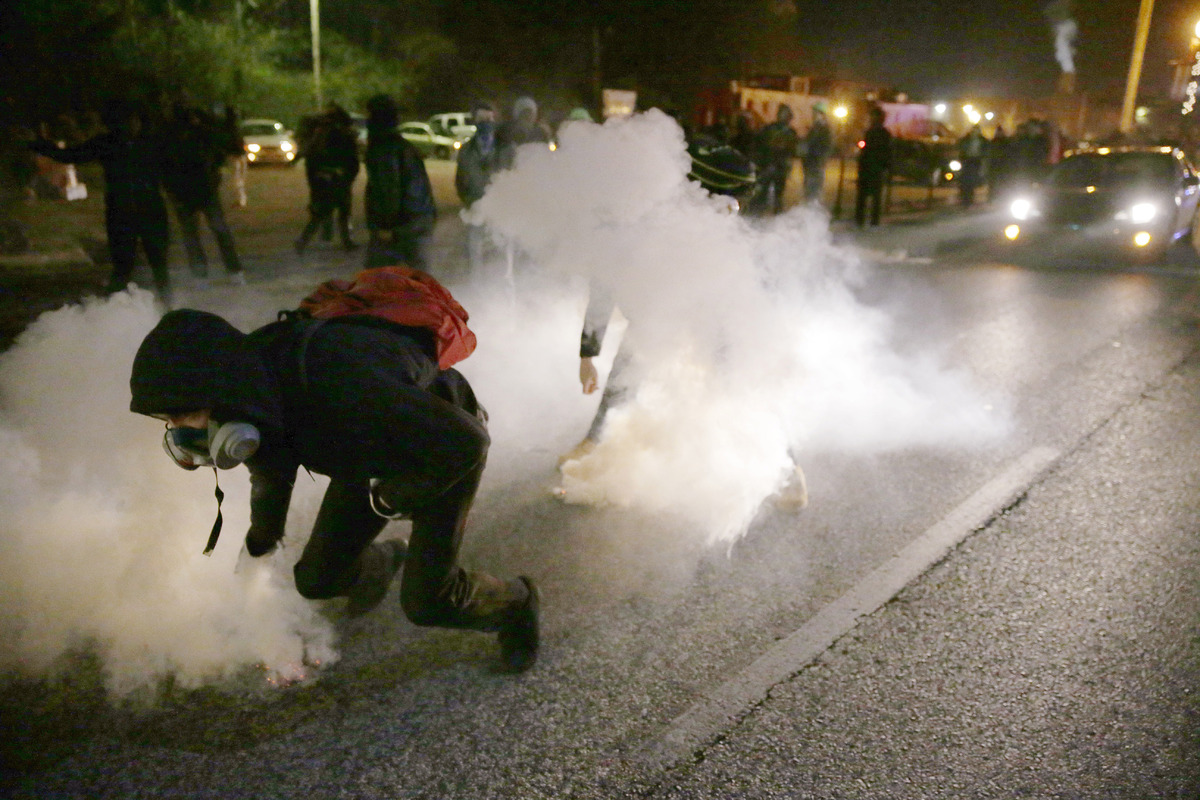 Protesters grab smoke canisters and throw them to police Tuesday, Nov. 25, 2014, in Ferguson, Mo. Missouri's governor ordered