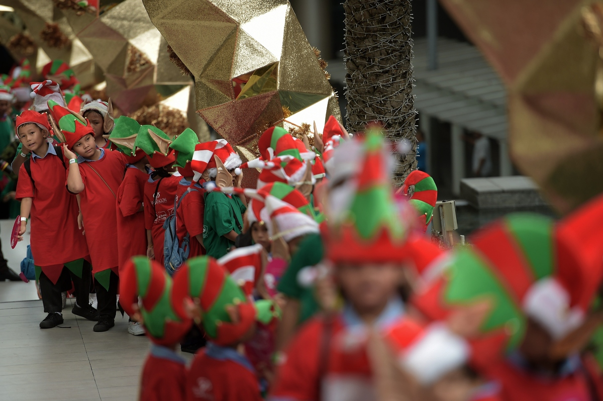 People dressed as Santa's elves gather outside a shopping mall to break a Guinness world record in Bangkok on November 25, 20