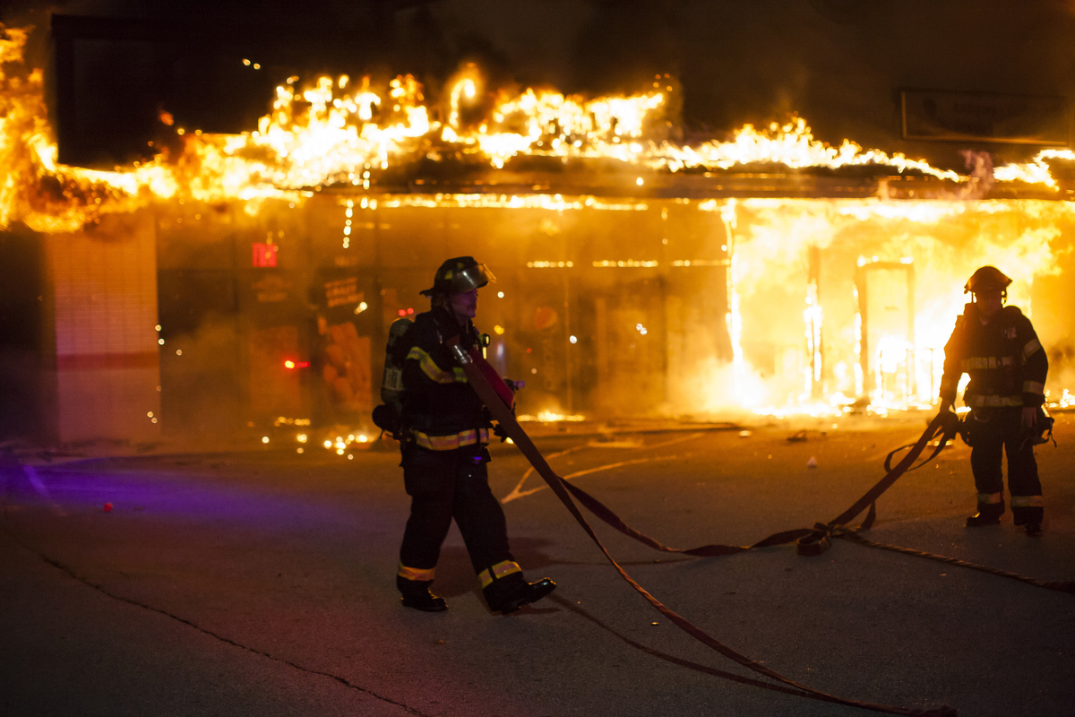 Firefighters attempt to put out a burning building during riots after grand jury's decision not to indict a police officer Da