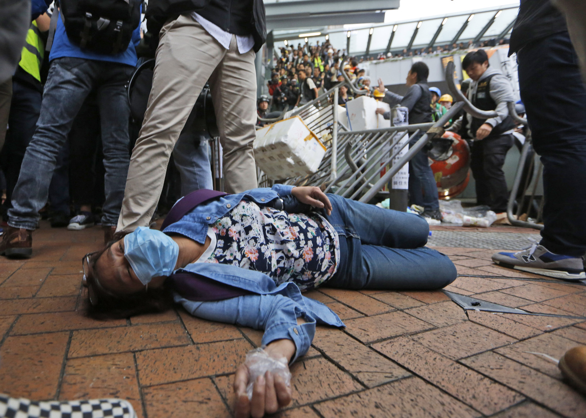 An injury protester lies on the ground during a police operation to remove protesters near government headquarters in Hong Ko
