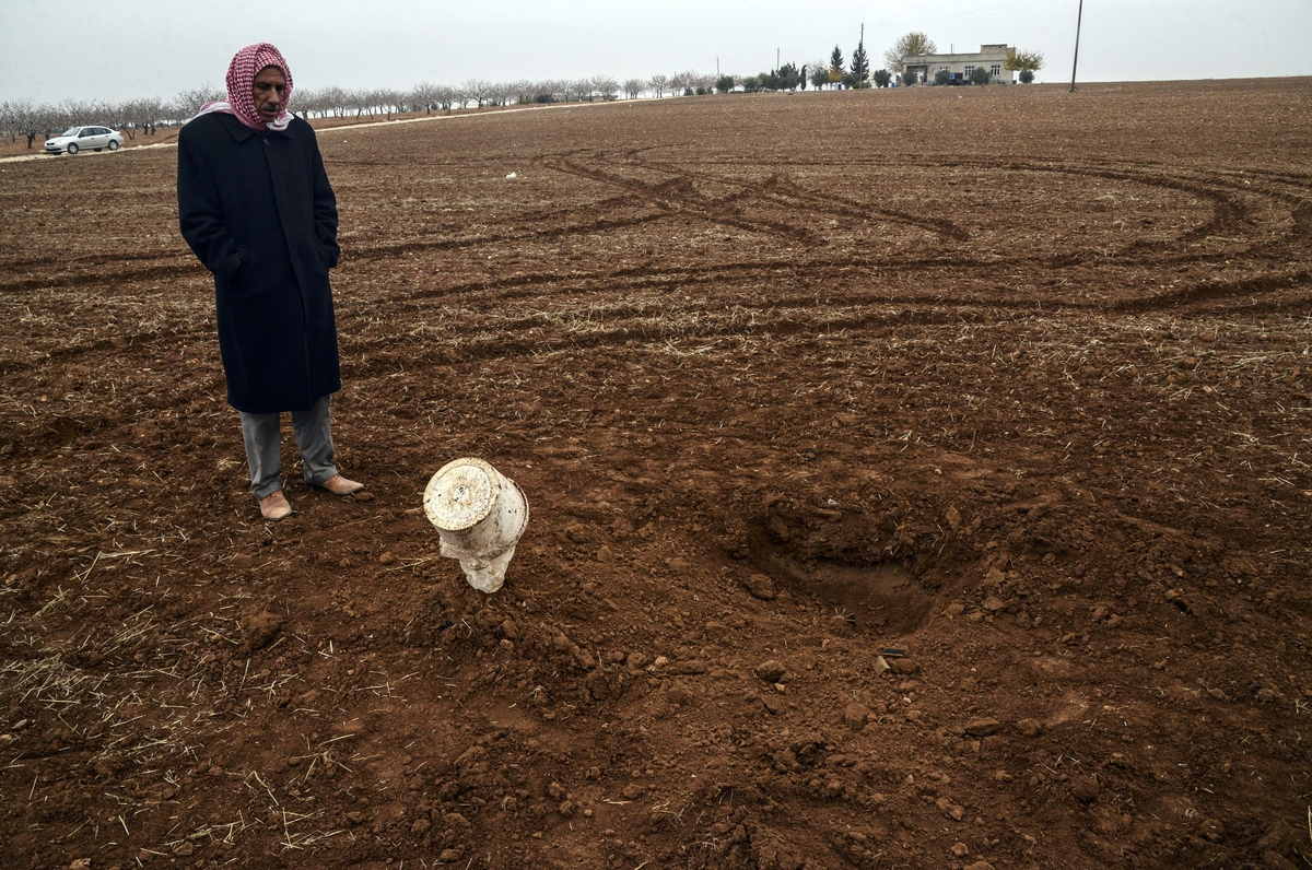 A Syrian refugee looks at a mortar shell that landed on the Turkish side of the border with Syria near Mursitpinar in the San