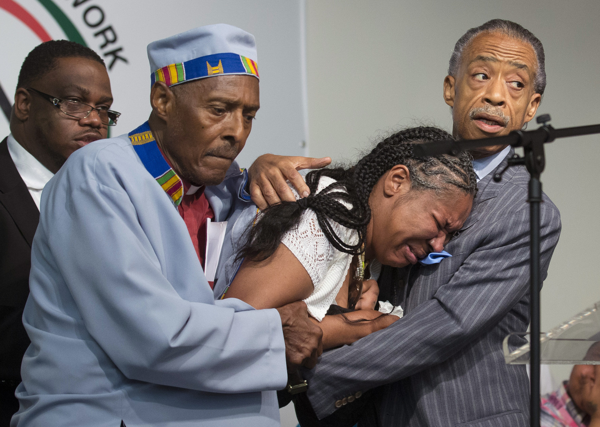 FILE - In this July 19, 2014, file photo, Esaw Garner, center, wife of Eric Garner, breaks down in the arms of Rev. Herbert D