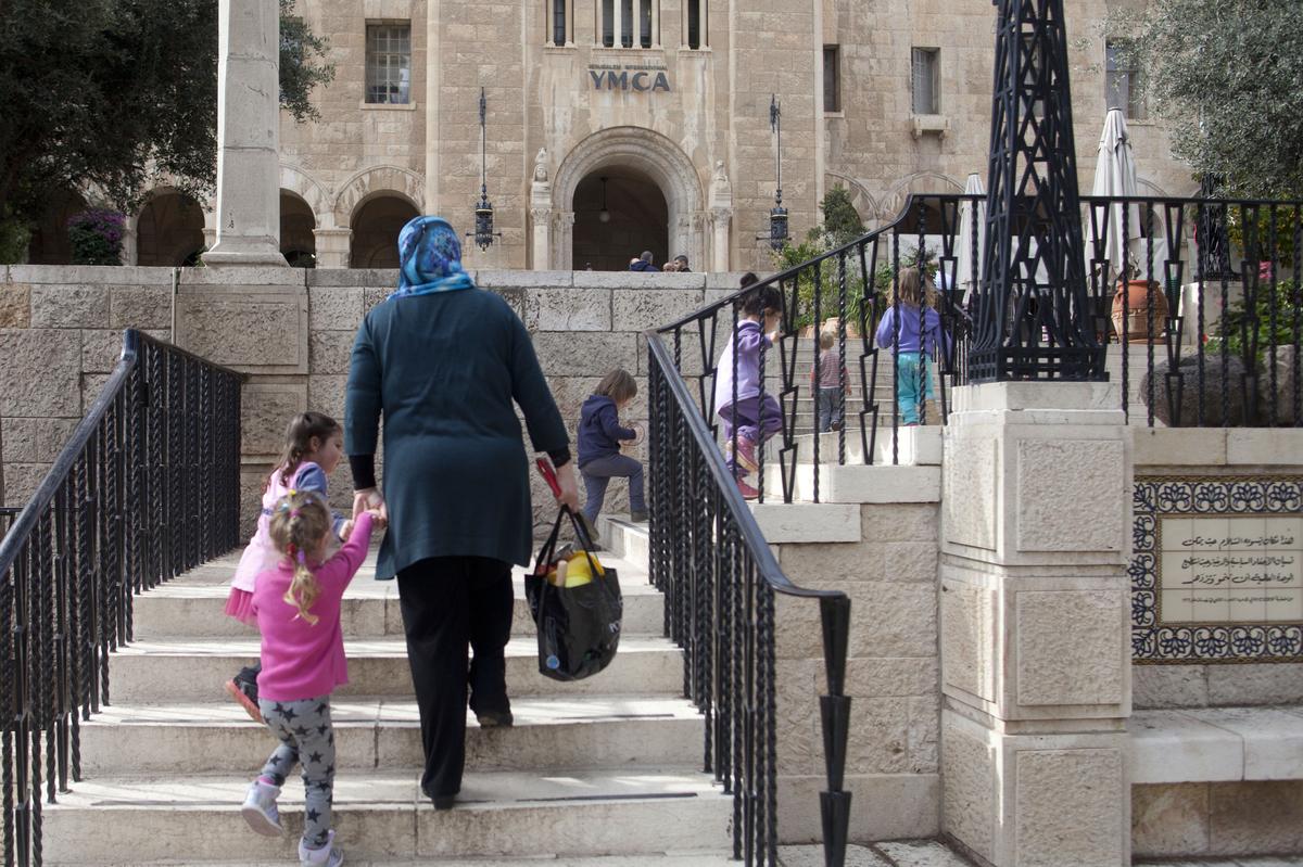 Nidal, a teacher at the YMCA kindergarten, holds children on December 3, 2014 in Jerusalem, Israel. In the Jerusalem Internat