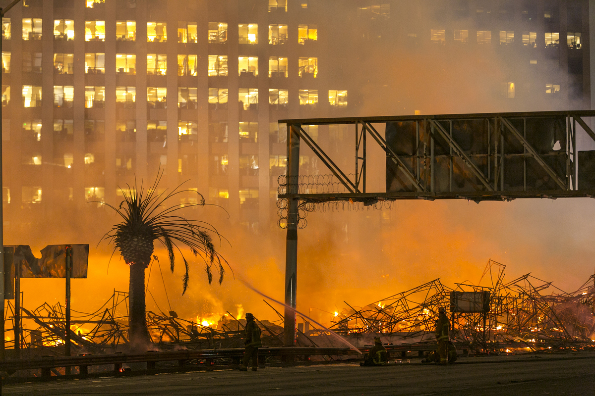 Los Angeles County firefighters battle a fire at an apartment building under construction next to the Harbor CA-110 Freeway i