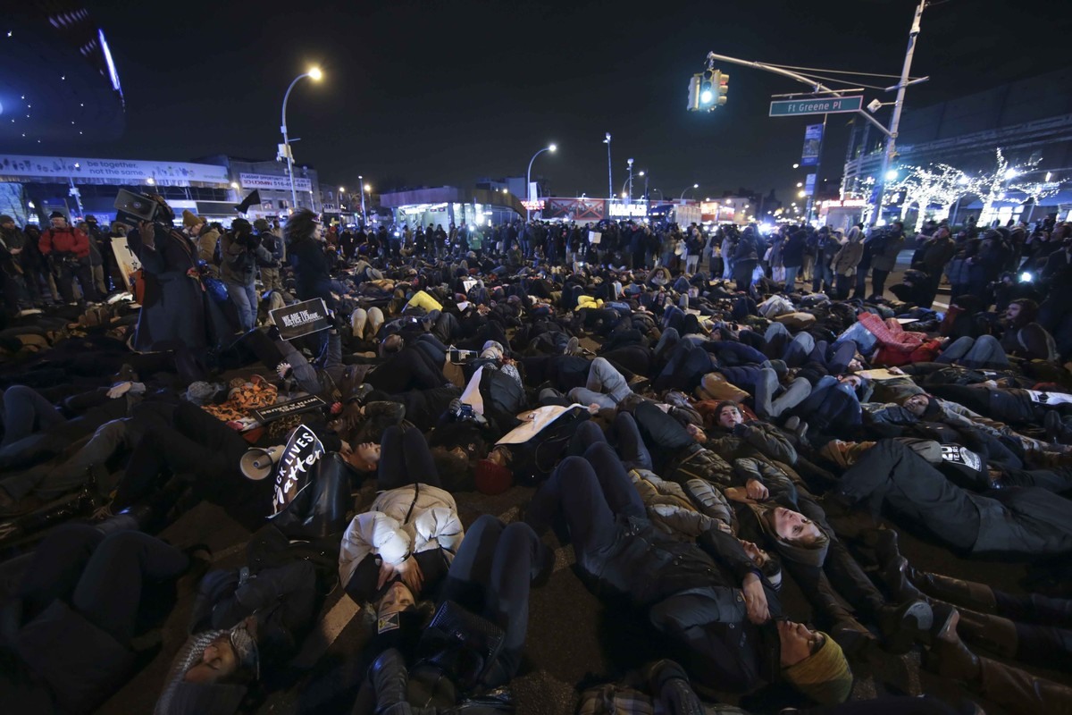 """Protesters conduct a """"die-in"""" in front of the Barclays Center after a grand jury decided not to indict the police officer inv"""