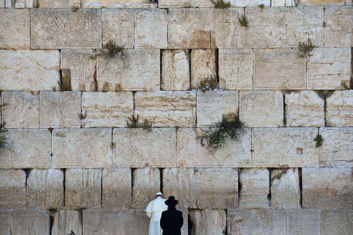 Pope Francis (L) prays as a Jewish Rabbi looks on at the Western Wall, Judaism's holiest site, in Jerusalem's Old City on May