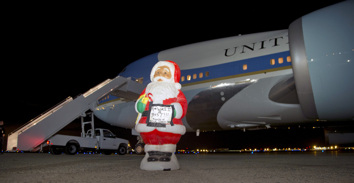 "A Santa figurine with a sign that says ""Hawaii or Bust"" stands on the tarmac in front of Air Force One before President Barac"