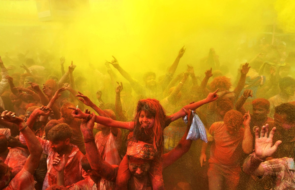 Indian revellers cover each other with coloured powder and dance while taking part in Holi festival celebrations in Guwahati