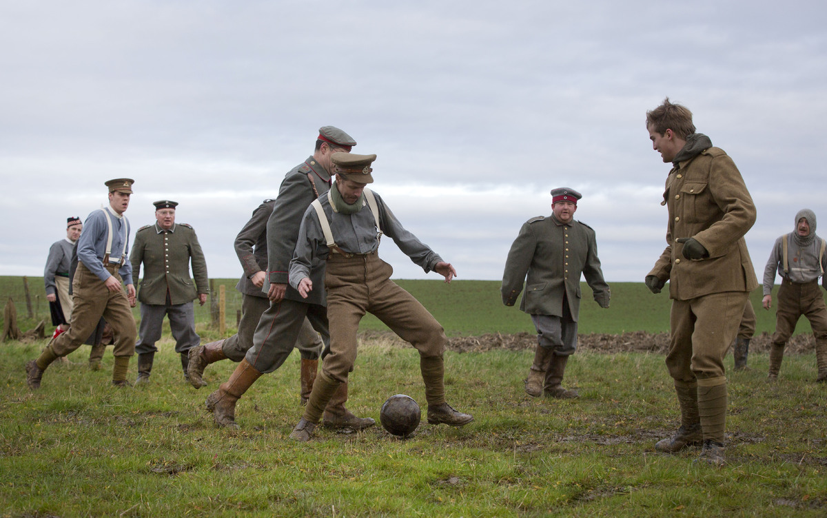 Re-enactors, from various living history groups, are dressed in World War I British and German uniforms as they kick around a