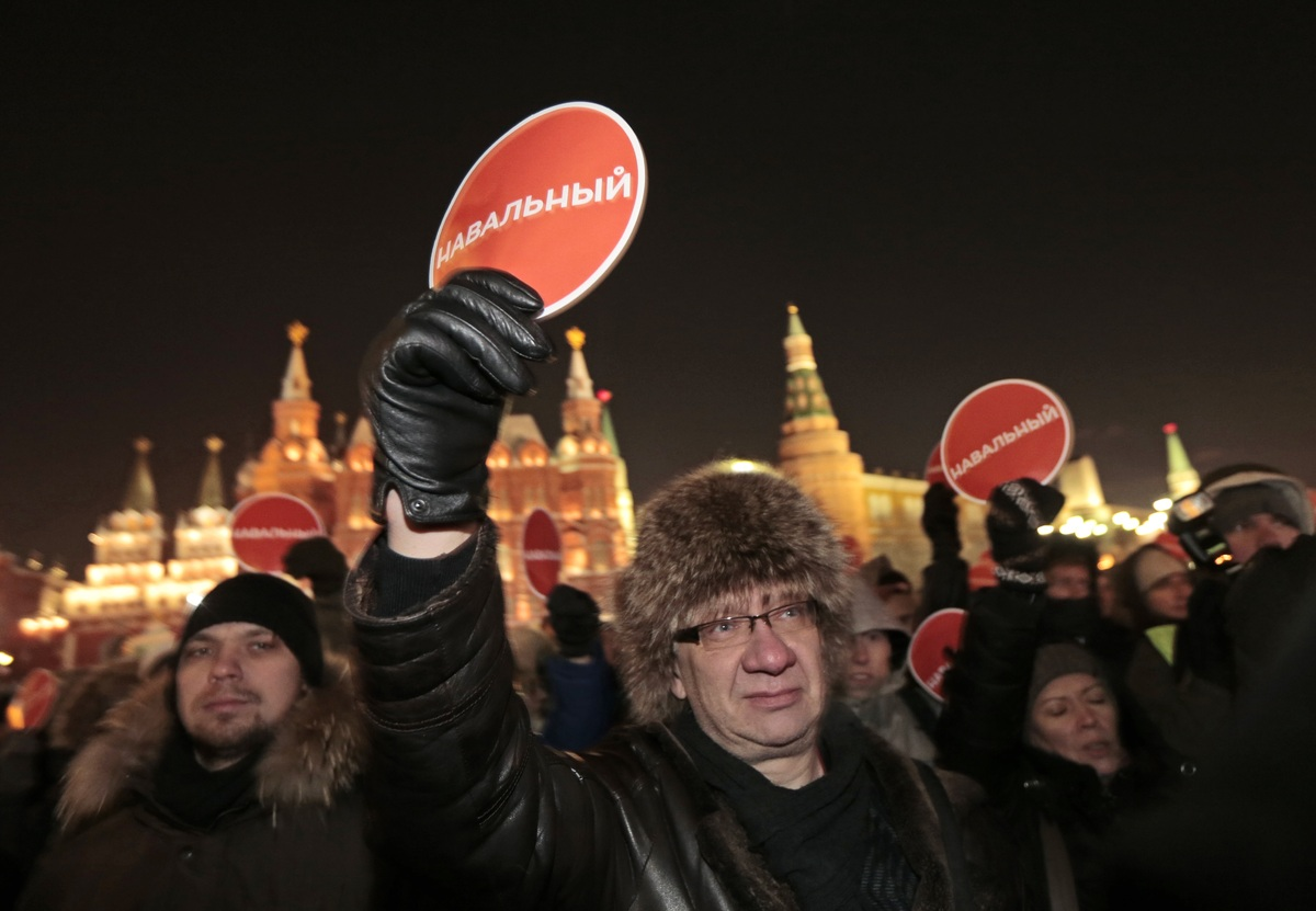 """Supporters of Russian opposition activist and anti-corruption crusader Alexei Navalny gather holding red posters reading """"Nav"""