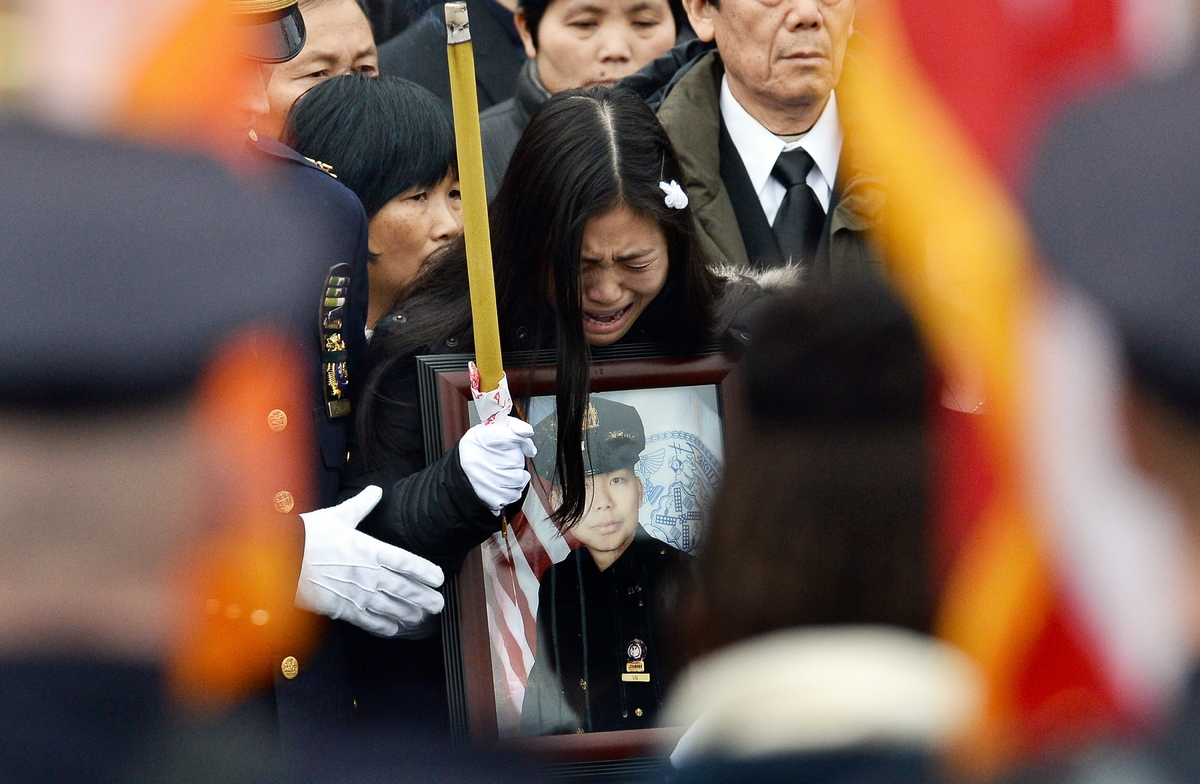 Pei Xia Chen (C) widow of New York Police Department (NYPD) officer Wenjian Liu cries holding a picture of her husband during