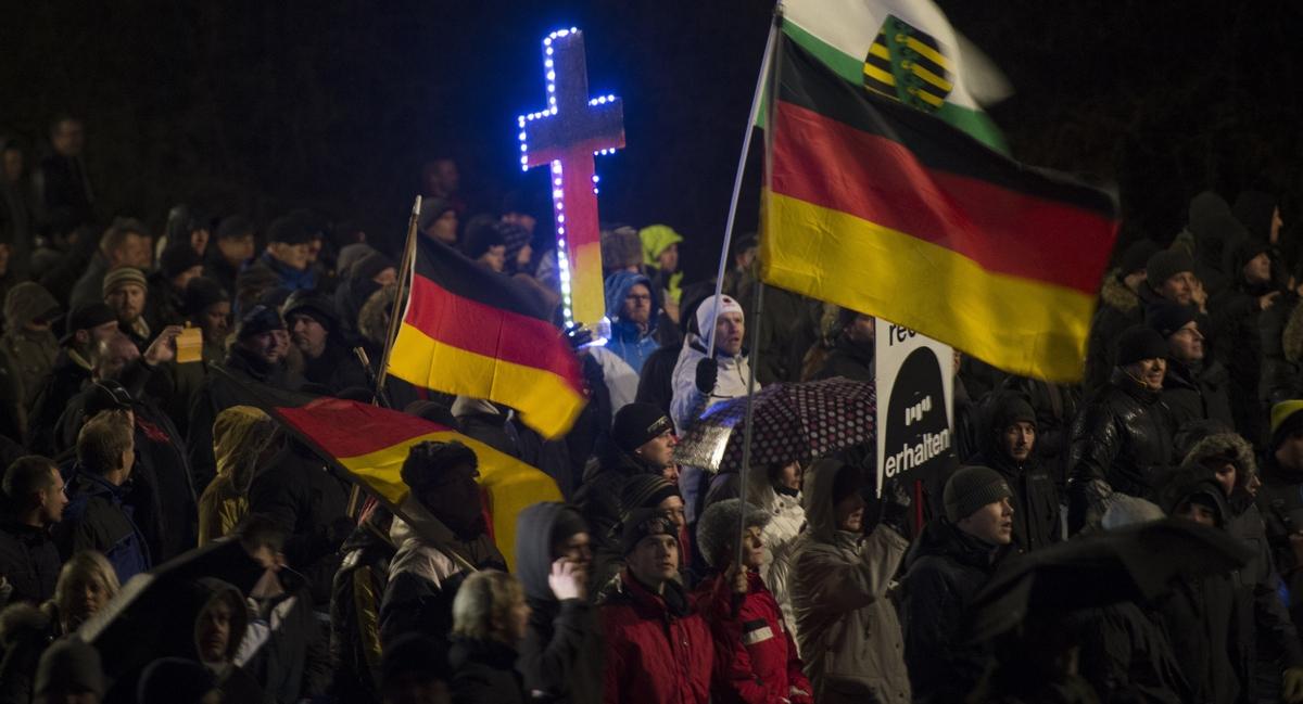 ドイツ国旗の色に塗られた十字架を掲げながらデモ行進をする反移民デモ参加者。このデモは、勢力を拡大している右派ポピュリスト団体のPEGIDAが2015年1月5日、ドイツ東部のドレスデンで行ったものだ。(ROBERT MICHAEL/AFP/Getty