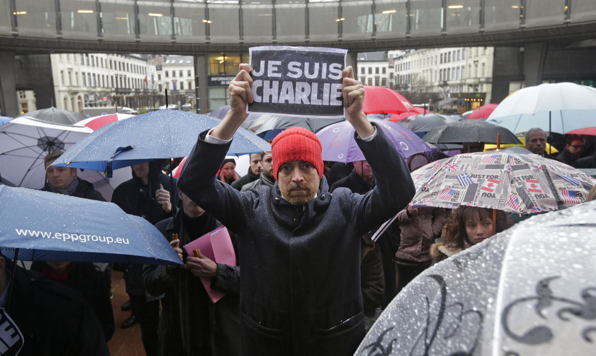 "A man shows a sign that reads: ""Je suis Charlie (I Am Charlie)"", during a gathering to pay respects to the victims of Wednesd"