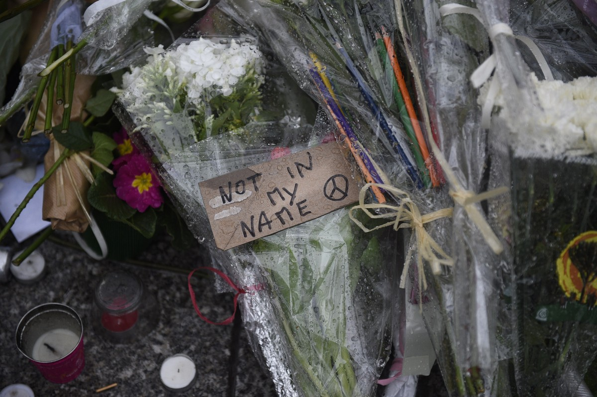 Floral tributes are laid on the ground during a minutes silence in Paris on January 8, 2015, at the site where Islamist gunme