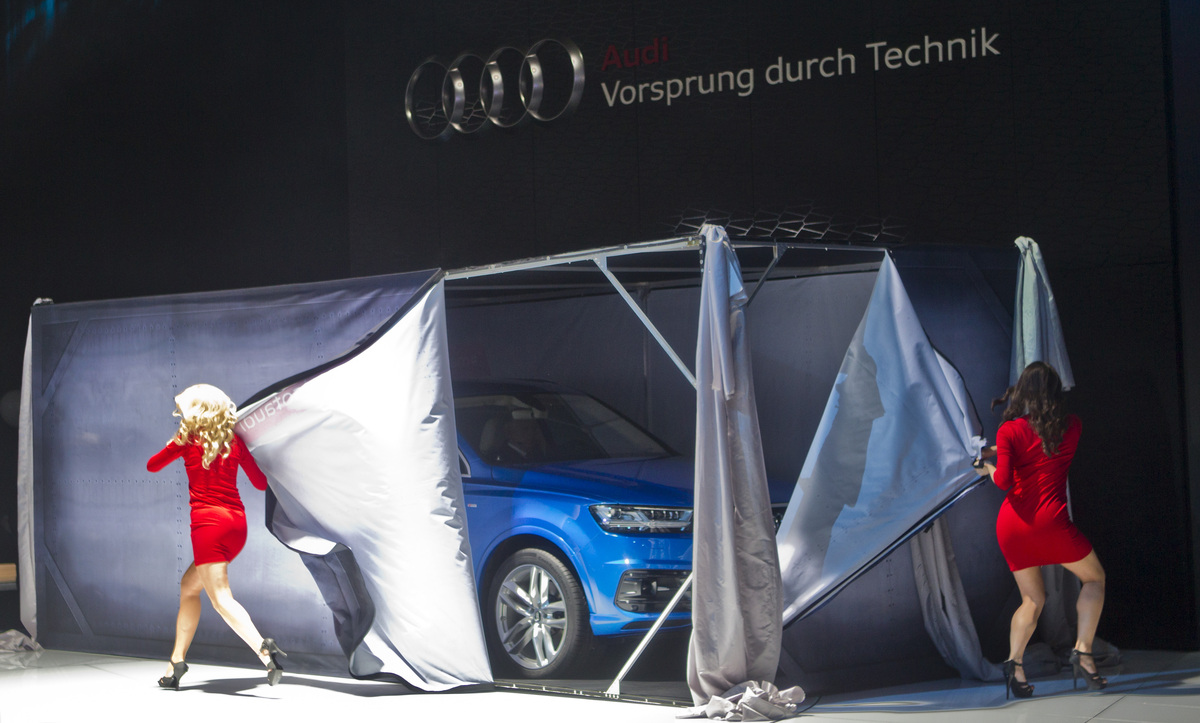 Models peel the sides away of a box unveiling the new Audi Q7 SUV inside, at the North American International Auto Show, Mond