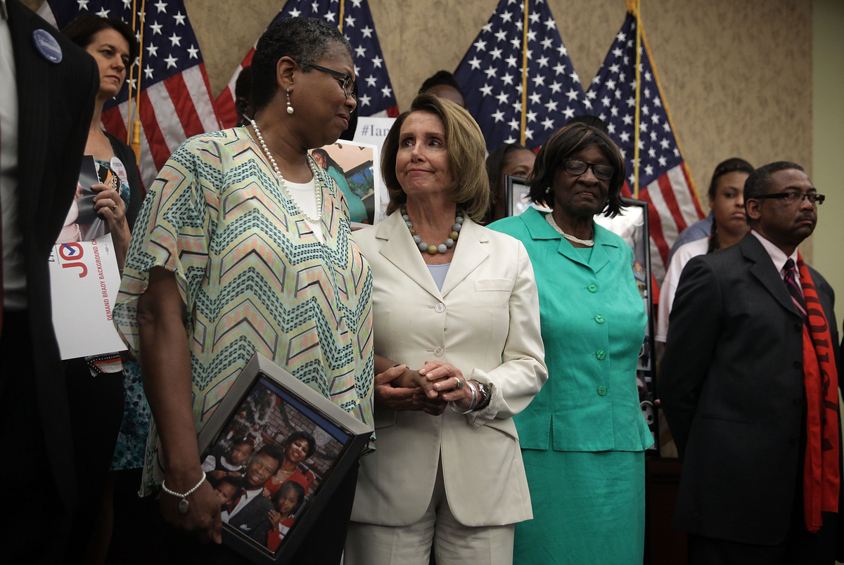 U.S. House Democratic Leader Nancy Pelosi (D-Calif.), center, hold hands with Sherialyn Byrdsong of Atlanta, Georgia, whose h