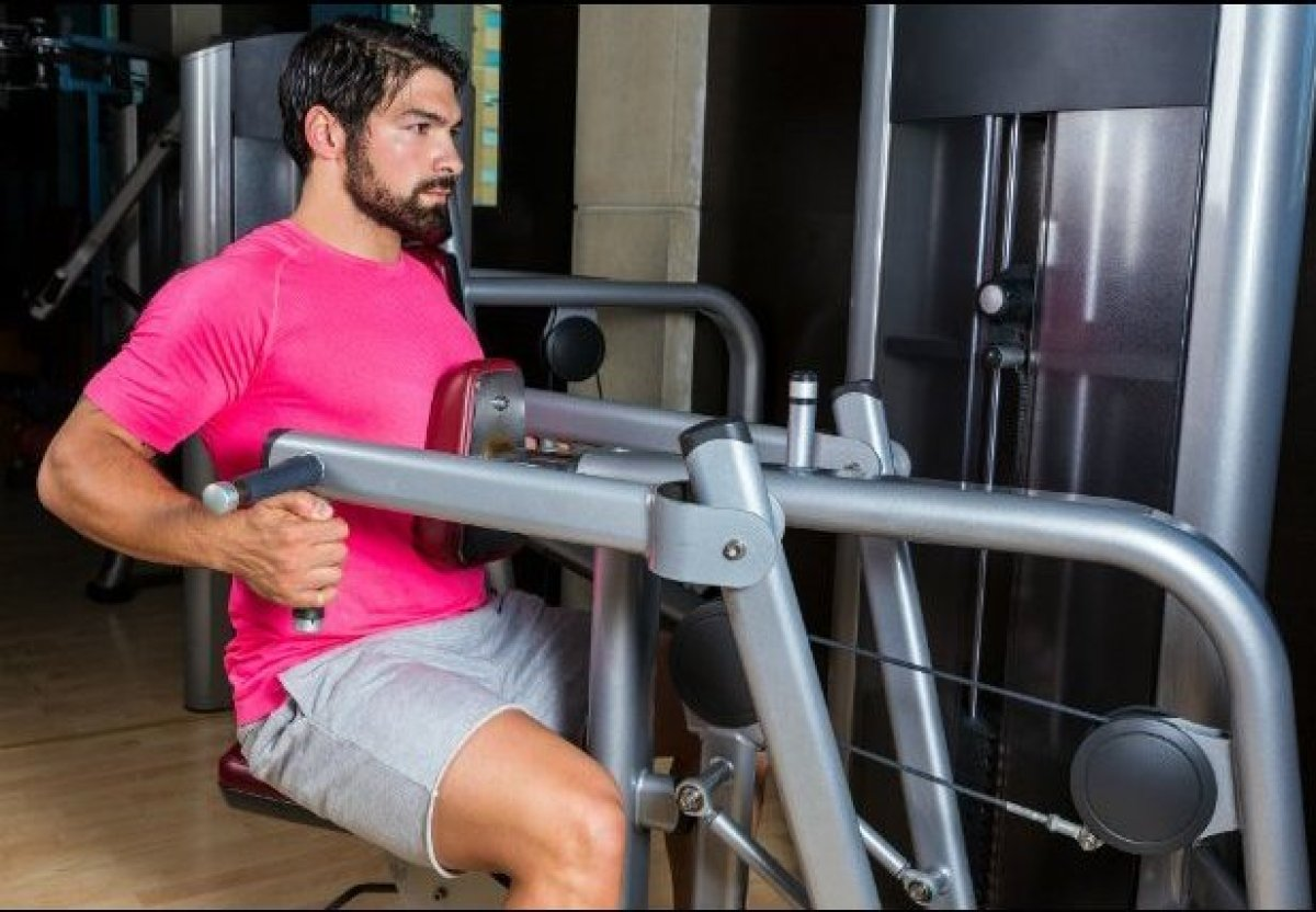 This exercise mainly targets muscles in the back and shoulders. However, instead of assuming a seated position (something you