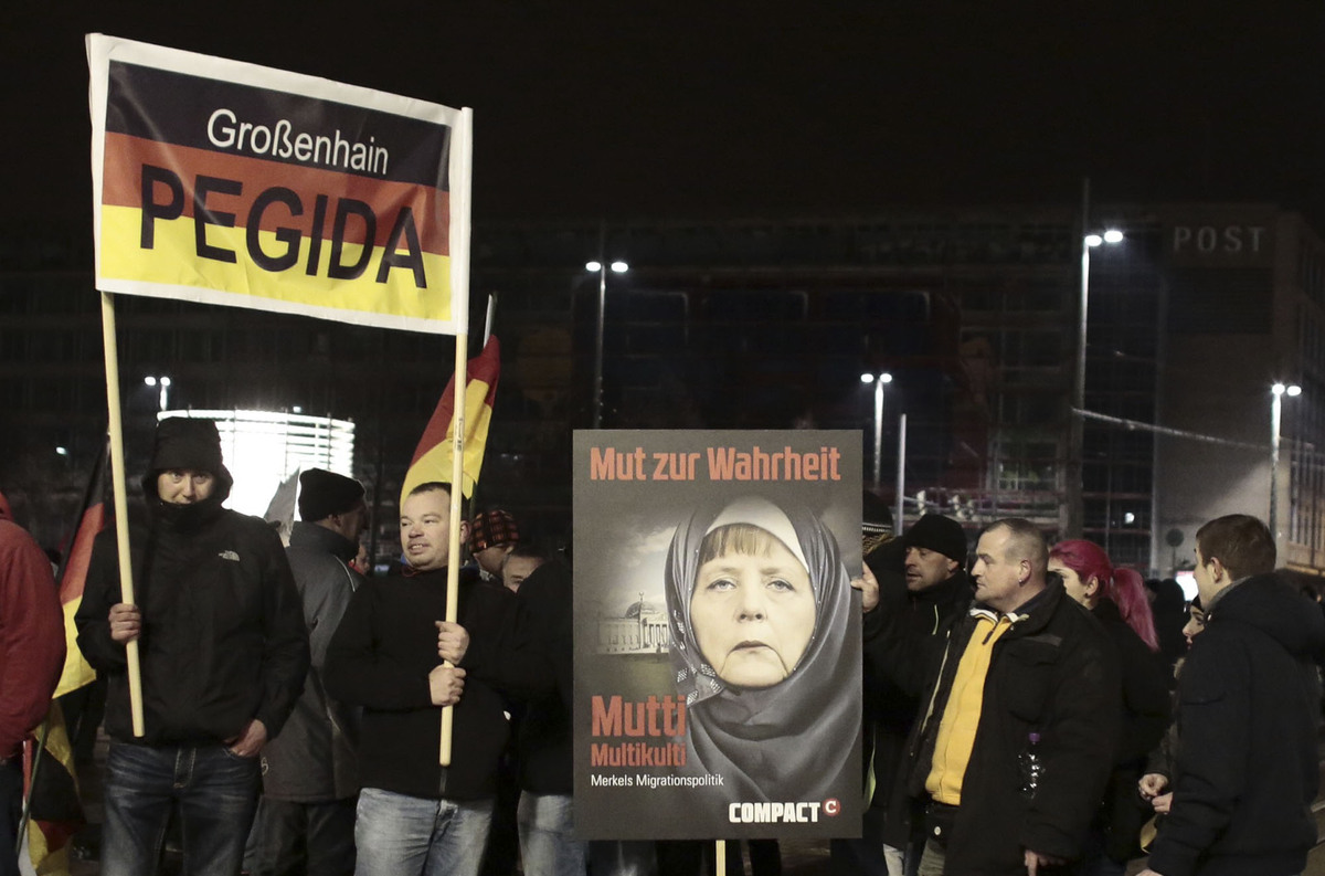 "People hold a poster depicting German Chancellor Angela Merkel wearing a veil and the writing ""Courage for truth - Mother Mul"