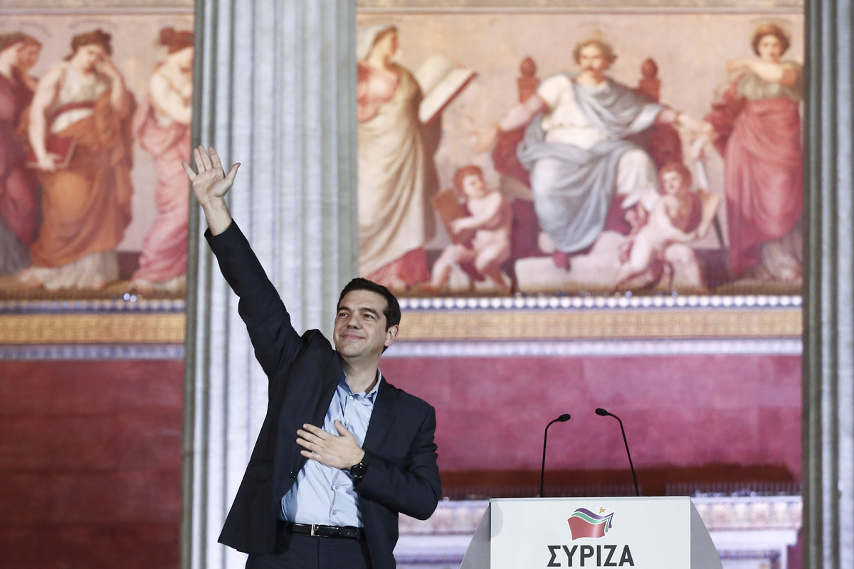 Leader of Syriza left-wing party Alexis Tsipras waves to his supporters outside Athens University Headquarters, Sunday, Jan.