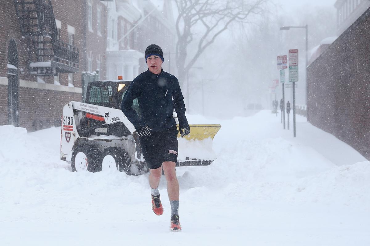 CAMBRIDGE, MA - JANUARY 27: A pedestrian runs through Cambridge as snow is cleared on January 27, 2015 in Cambridge, Massachu
