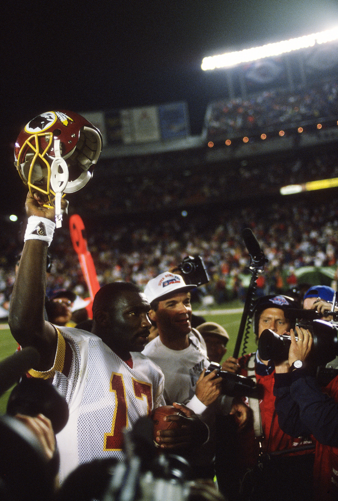 SAN DIEGO, CA- JANUARY 31:  Doug Williams #17 of the Washington Redskins walks off the field holding his helmet in the air af