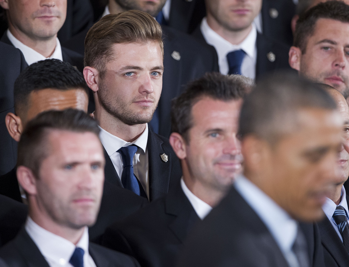 Galaxy's Robbie Rogers, left, listens to President Barack Obama, right, speak during a ceremony honoring both 2014 NHL Champi