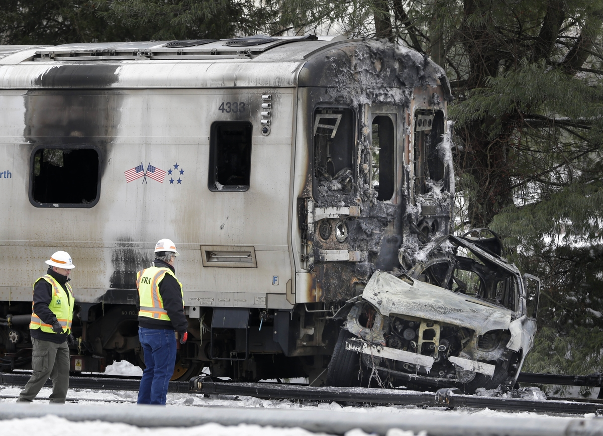 Authorities wearing Federal Railroad Administration vests look over the wreckage of a Metro-North Railroad train and a SUV in