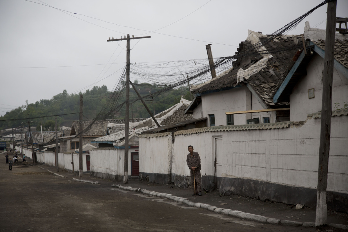 In this June 20, 2014 photo, a North Korean man stands in front of a row of homes in the town of Kimchaek, in North Korea's N